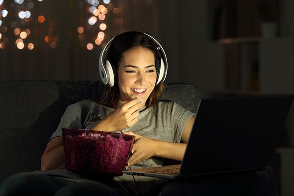 Lady eating popcorn, watching movie.